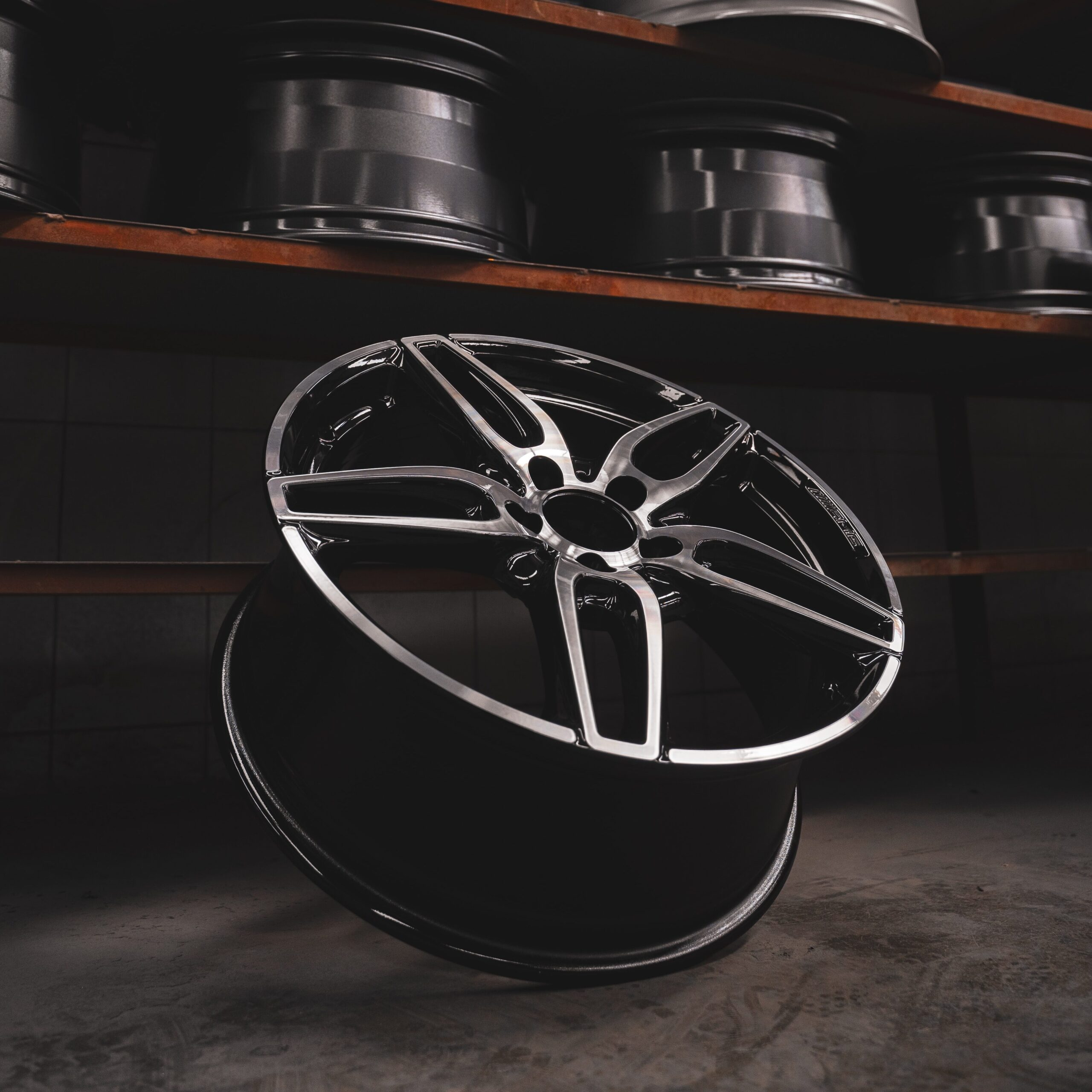 Silver car wheel facing upwards leaning against a shelf with other wheels