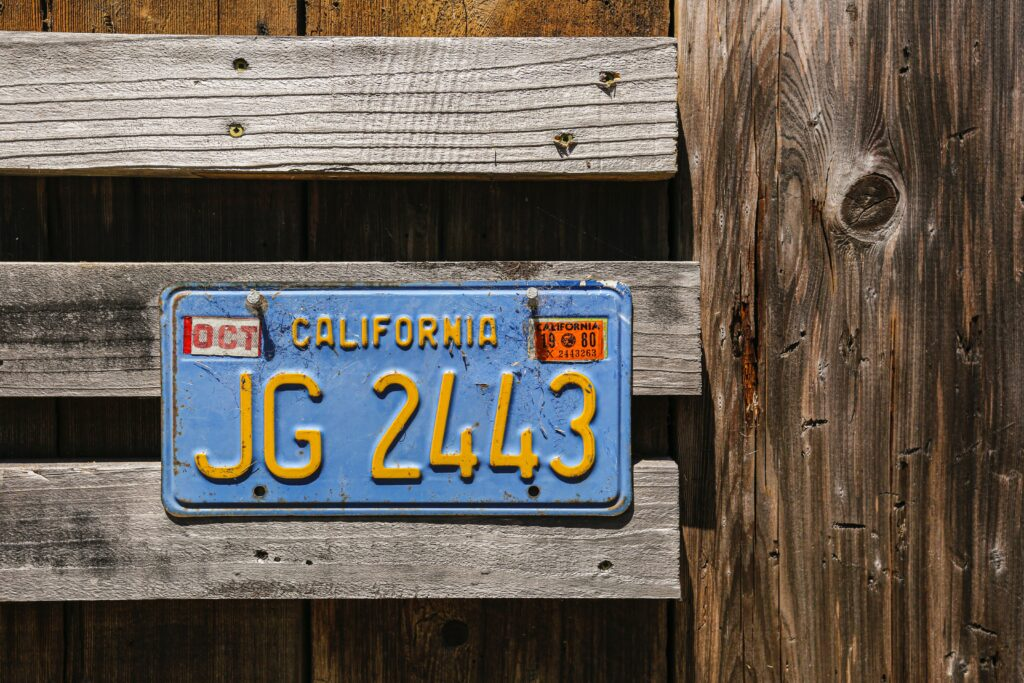 Blue car license plate with yellow text on a wooden fence