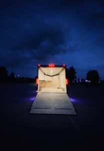 Large vehicle trailer with bed lowered in front on a dark blue sky